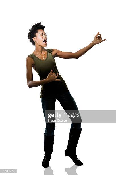 Portrait of a young woman playing air guitar