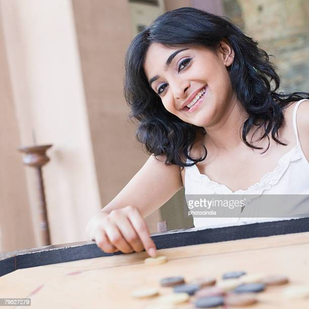 Portrait of a young woman playing carom and smiling