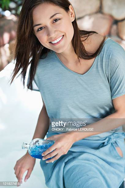 Portrait of a young woman pouring aromatherapy oil in bathtub