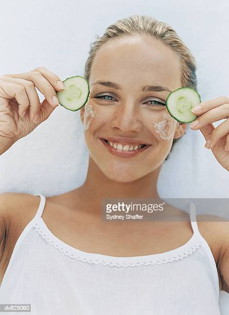 Portrait of a Young Woman Preparing for a Face Mask and Holding Slices of Cucumber
