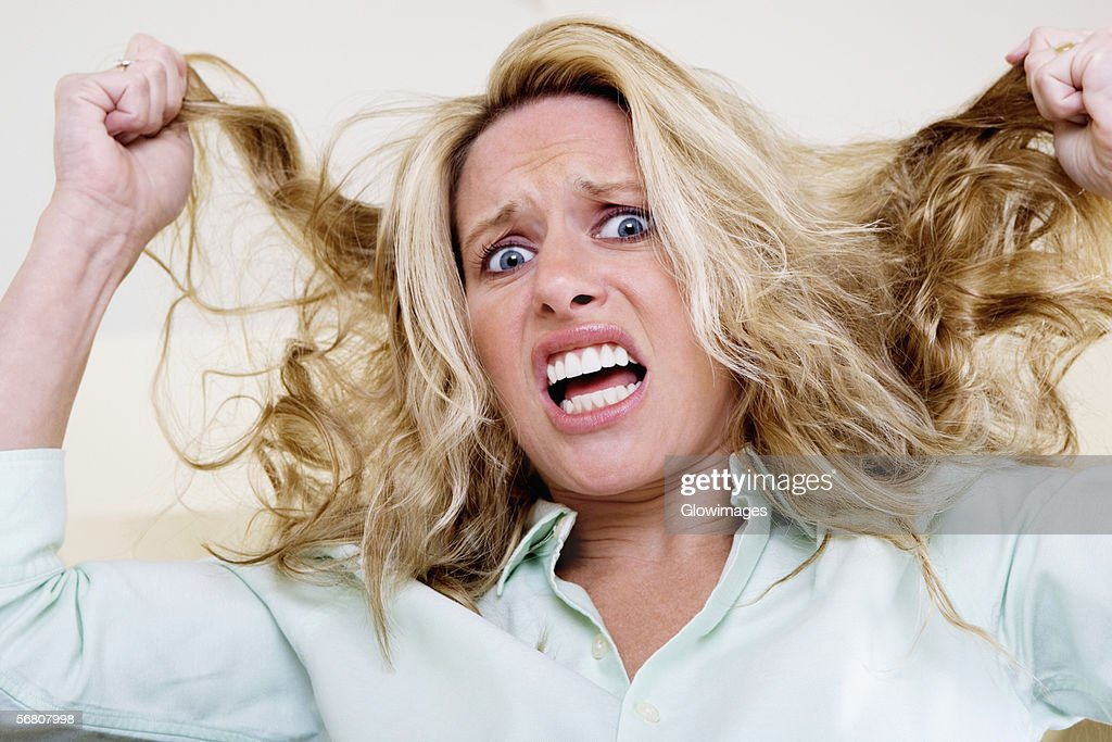 Portrait of a young woman pulling her hair : Stock Photo
