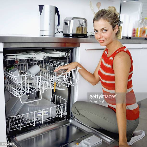 Portrait of a young woman putting dishes in a dishwasher