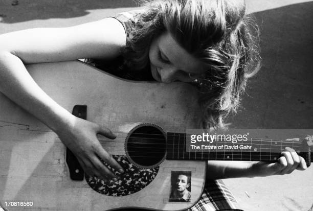 Portrait of a young woman rapturously playing an acoustic folk guitar in June 1965 in Washington Square Park Greenwich Village New York City New York...