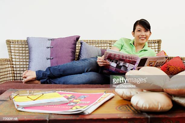 Portrait of a young woman reclining on a couch and holding a newspaper