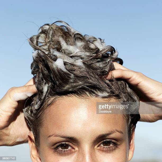 portrait of a young woman shampooing her hair