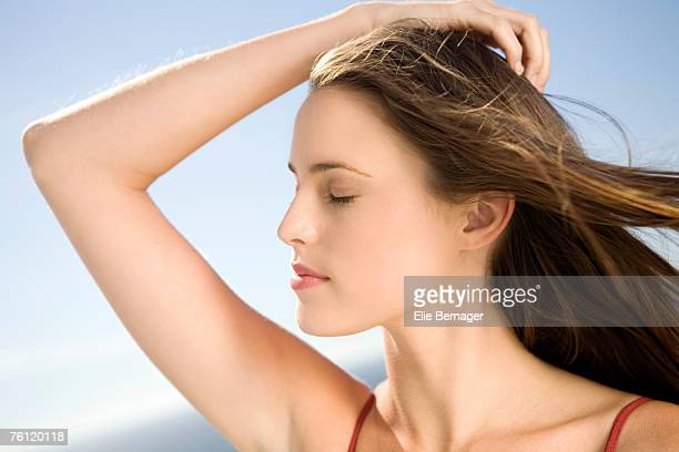 Portrait of a young woman, shut eyes, hand in her hair, outdoors