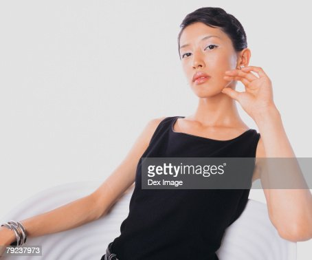 Portrait of a young woman sitting, Confident pose : Stock Photo