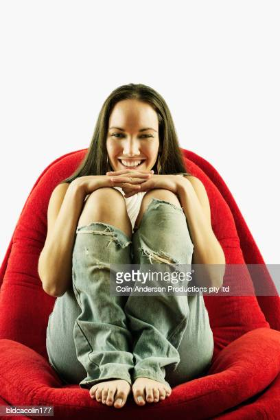 Portrait of a young woman sitting crouched on a chair smiling