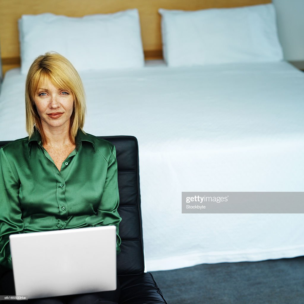 portrait of a young woman sitting in a bedroom using a laptop : Stock Photo
