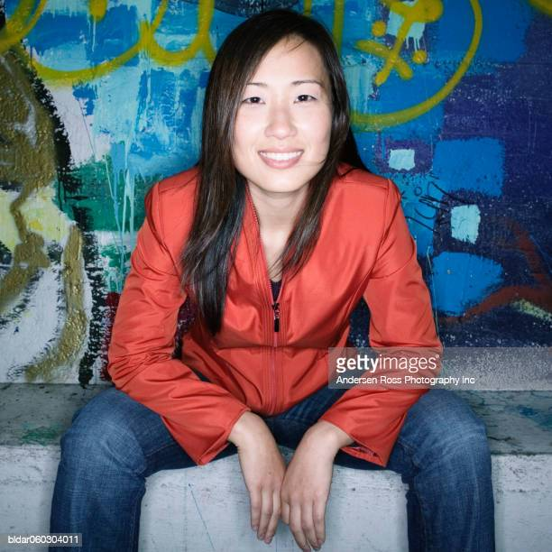 Portrait of a young woman sitting in front of a graffiti wall