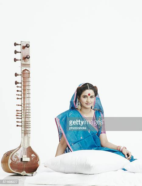 Portrait of a young woman sitting near a sitar