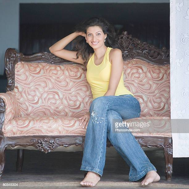 Portrait of a young woman sitting on a couch and smiling