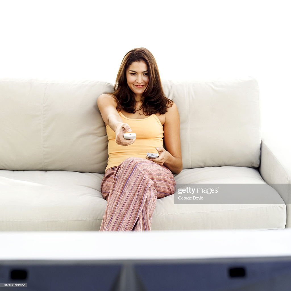 portrait of a young woman sitting on a couch watching television : Stock Photo