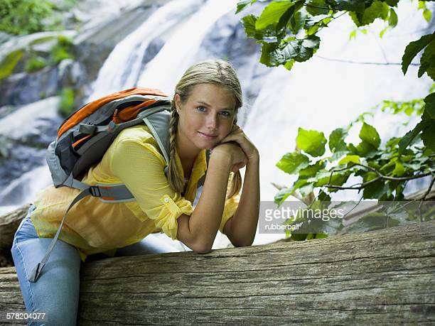 Portrait of a young woman sitting on a fallen tree