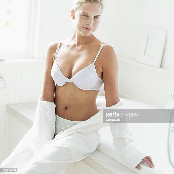portrait of a young woman sitting on the edge of a bathtub