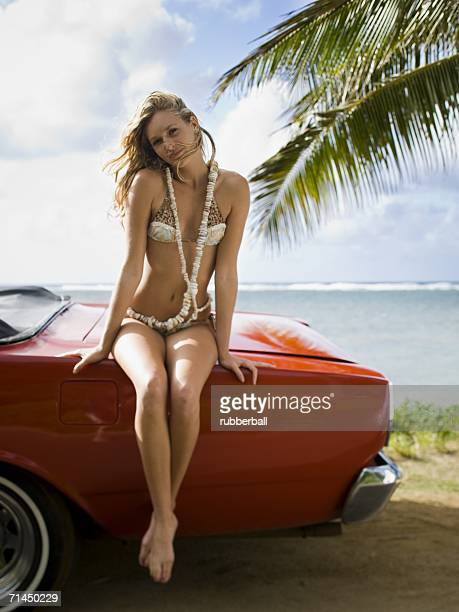 Portrait of a young woman sitting on the rear of the car