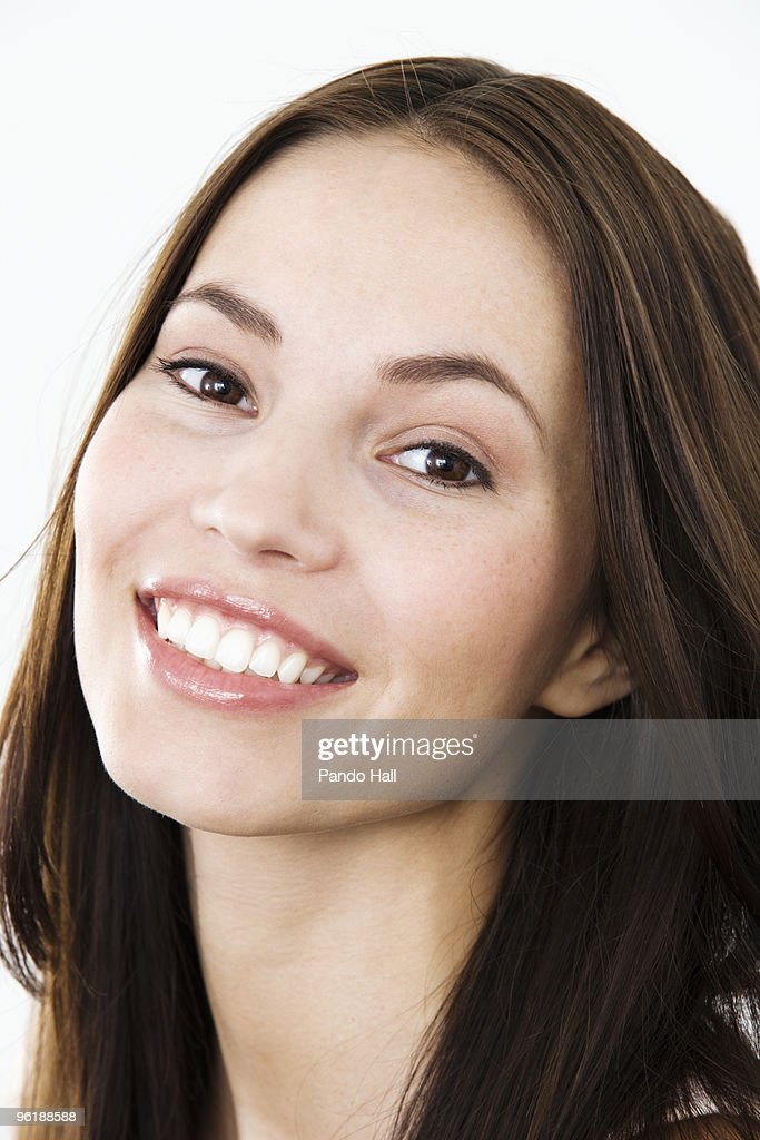 Portrait of a young woman smiling, close-up : Stock Photo