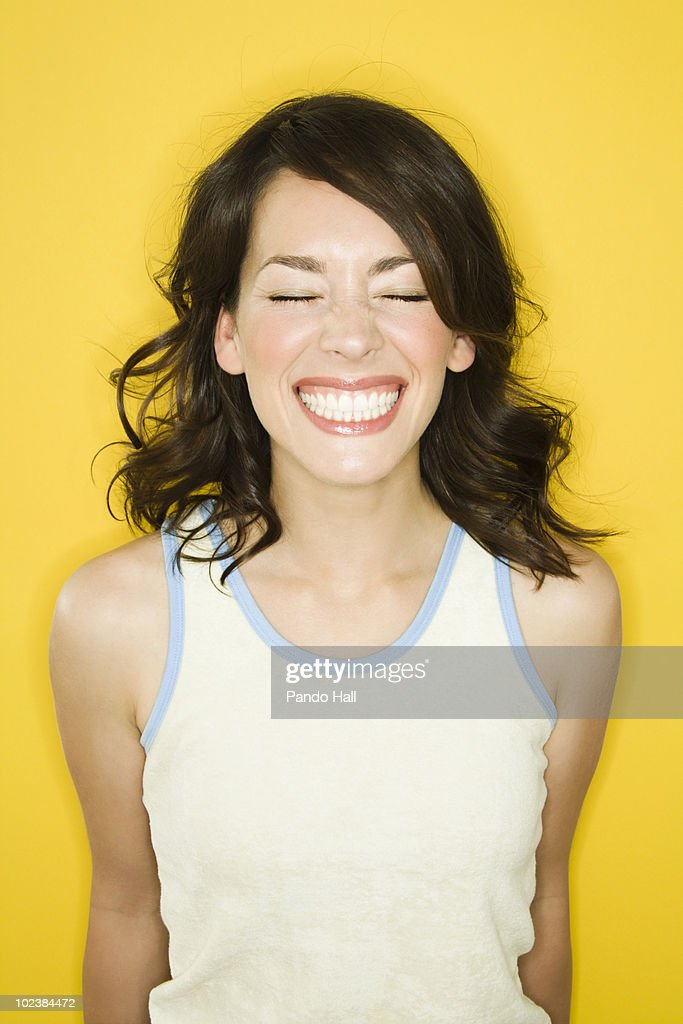 Portrait of a young woman smiling, eyes closed : Stock Photo