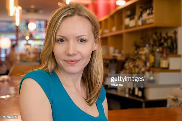 Portrait of a young woman smiling in a cafe