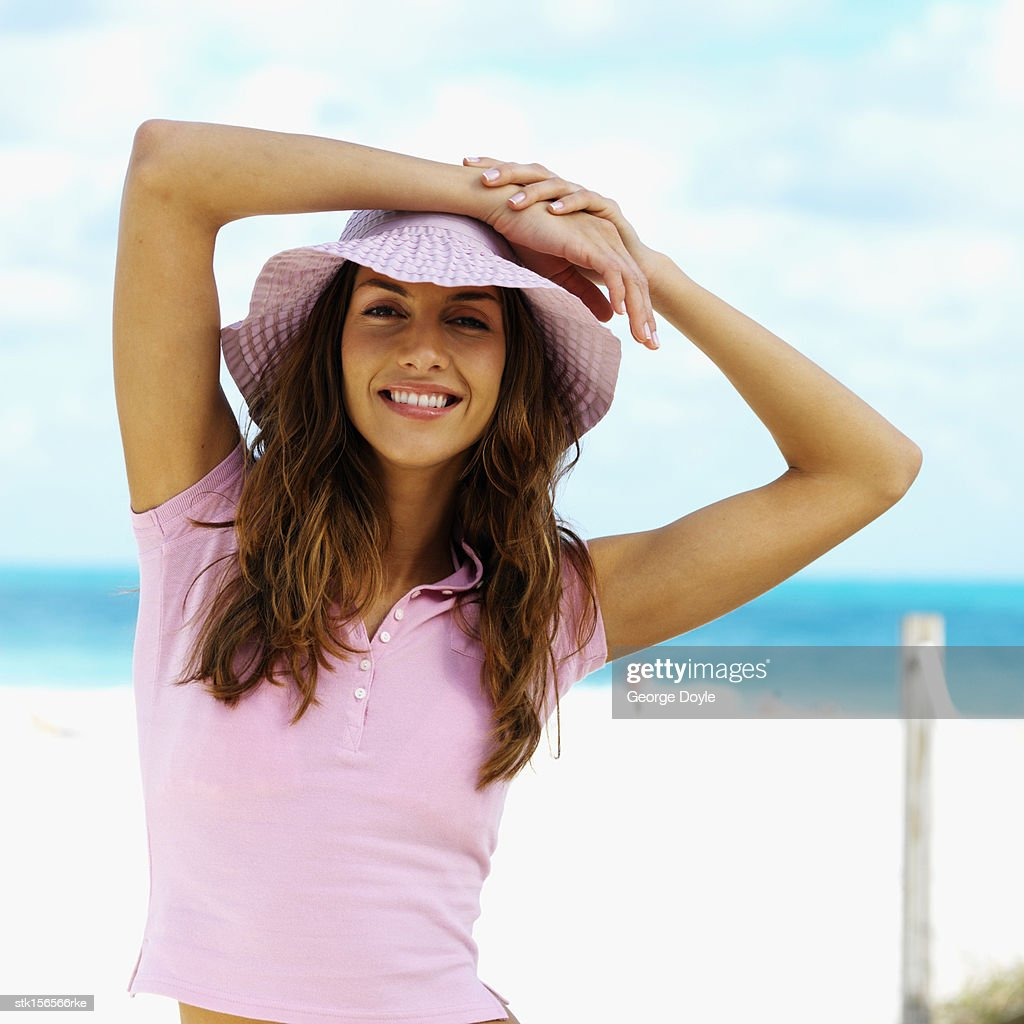 Portrait of a young woman smiling with her hands on her head : Stock Photo