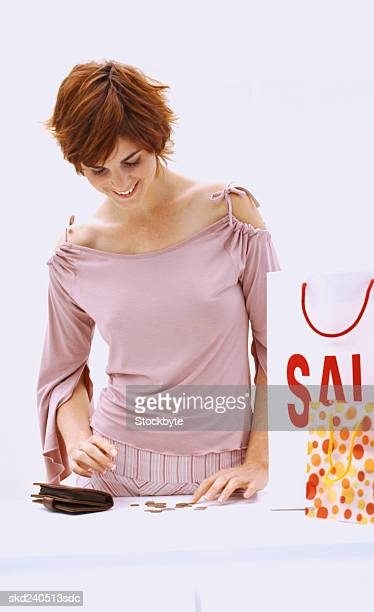 Portrait of a young woman standing beside a shopping bag