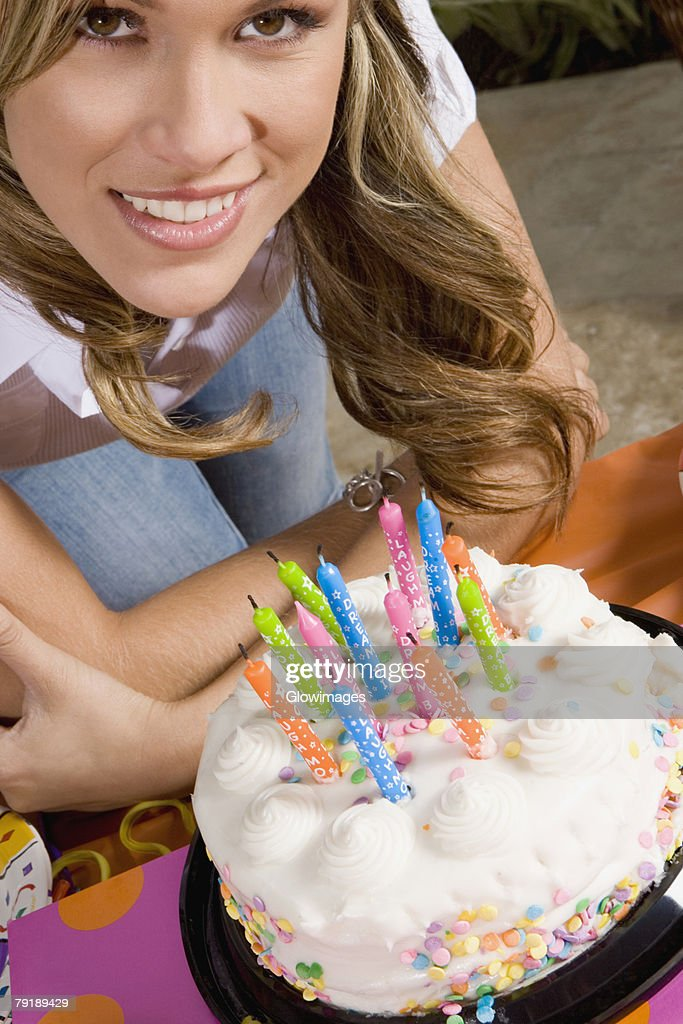 Portrait of a young woman standing in front of a birthday cake and smiling : Foto de stock