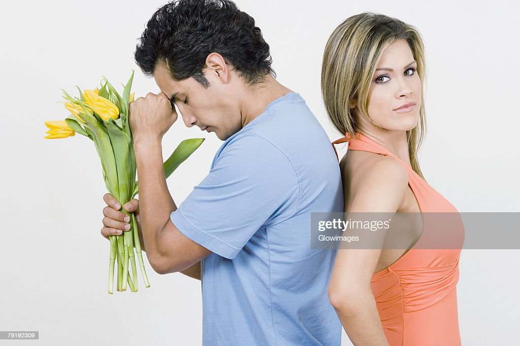 Portrait of a young woman standing with a young man holding flowers : Stock Photo