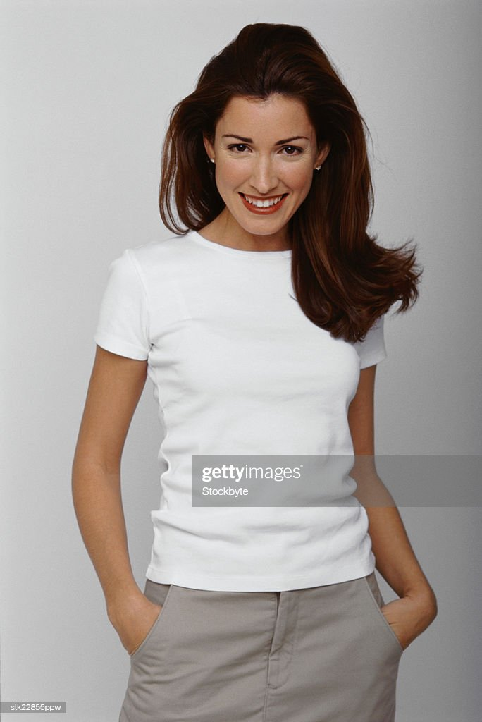 portrait of a young woman standing with her hands in her pockets : Stock Photo