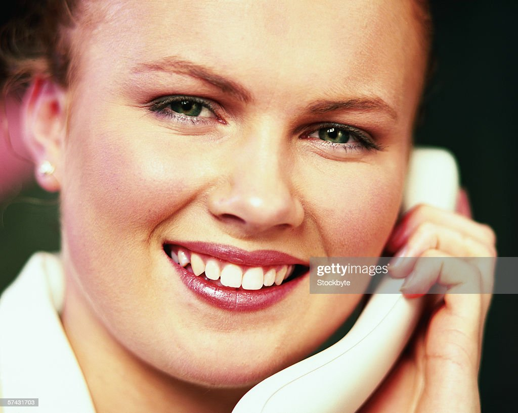 Portrait of a young woman talking on telephone : Stock Photo