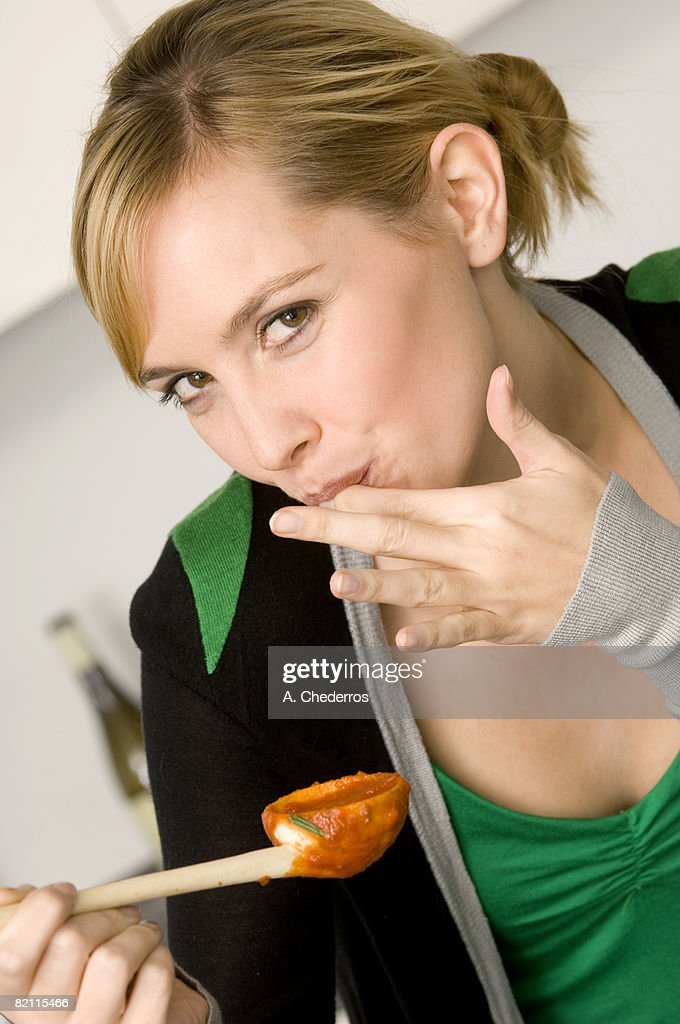 Portrait of a young woman tasting tomato sauce with her finger
