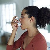 portrait of a young woman using an inhaler