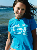 Portrait of a Young Woman Wearing a Blue T-Shirt With Text, Standing on the Beach, Smiling