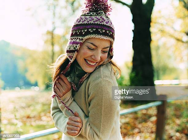 Portrait of a Young Woman Wearing a Bobble Hat Smiling With Her Arms in Front and Her Eyes Closed