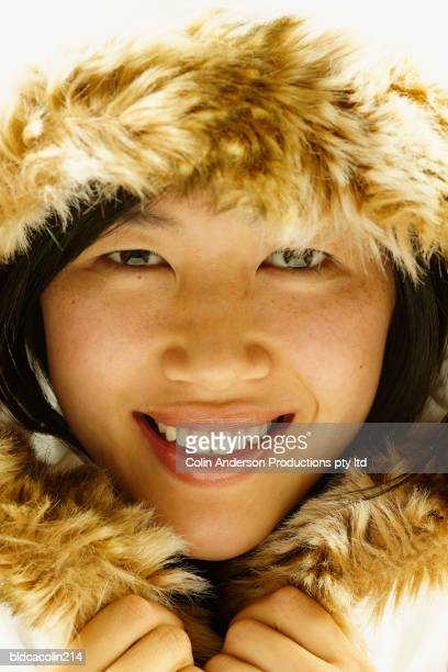 Portrait of a young woman wearing a furry hooded jacket