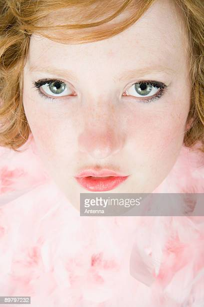 A portrait of a young woman wearing a pink feather boa
