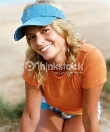 46178a06 Portrait of a Young Woman Wearing a Sun Visor Kneeling Outdoors : Stock  Photo