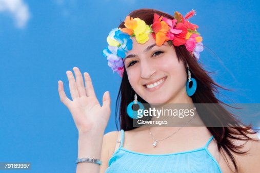 Portrait of a young woman wearing flowers and waving her hand : Foto de stock