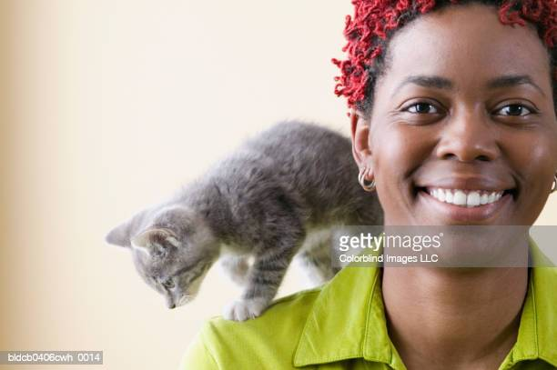 Portrait of a young woman with a kitten on her shoulder