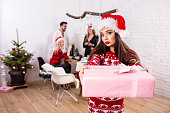 Portrait of a young woman with a pink giftbox on the foreground. Beautiful brunette in a Santa hat, red costume with deers. Christmas party at home.