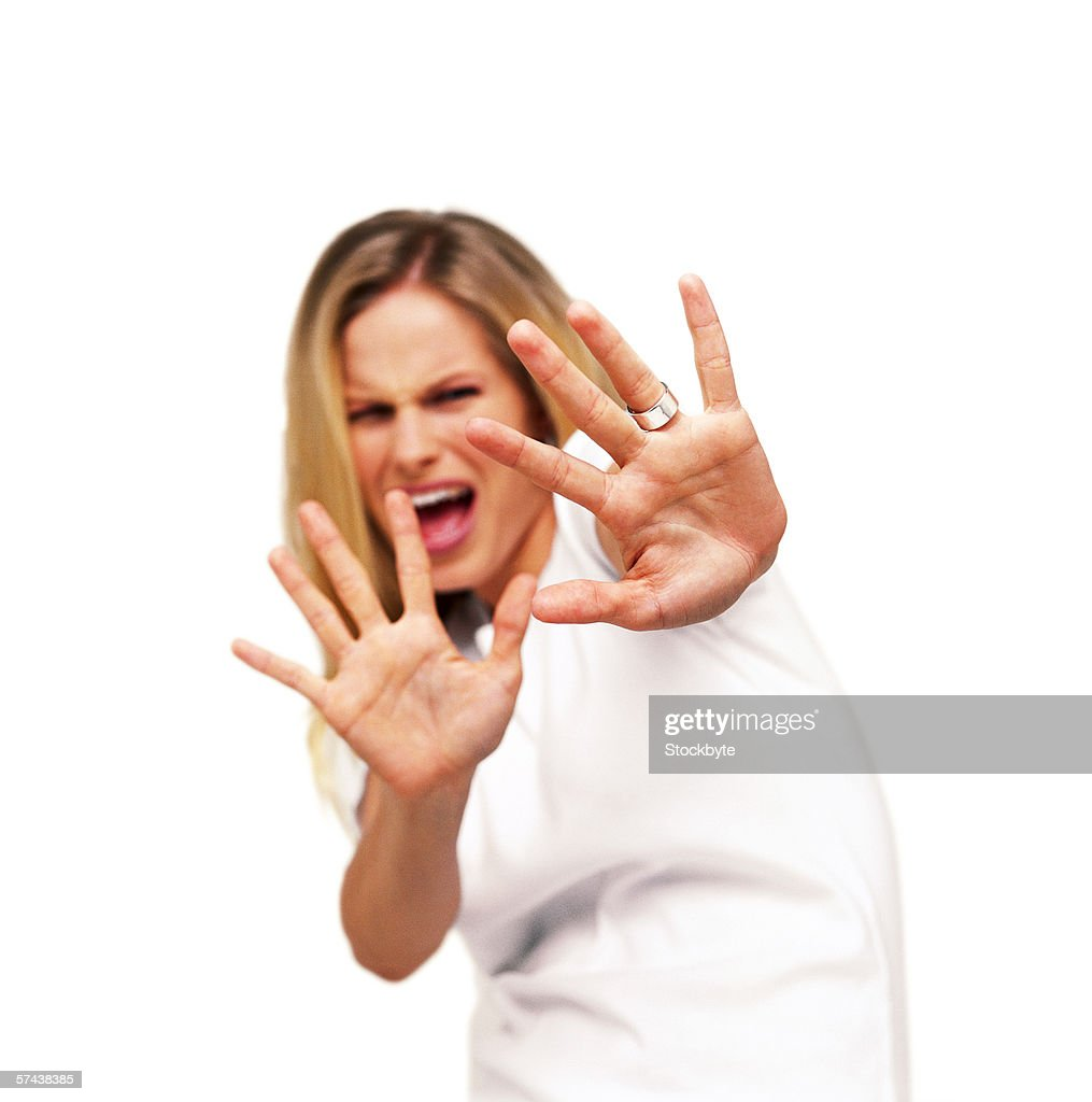 portrait of a young woman with her arms raised palms showing in fear : Stock Photo