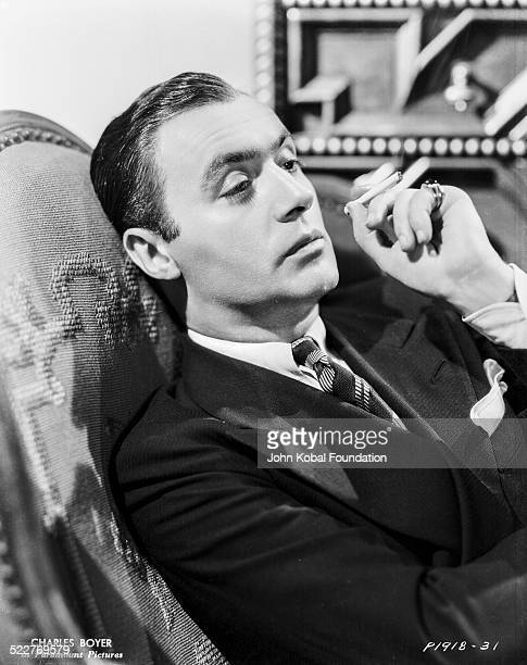 Portrait of actor Charles Boyer reclining in an armchair and smoking a cigarette for Paramount Pictures 1932