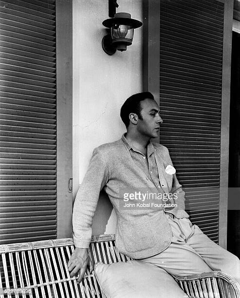 Portrait of actor Charles Boyer sitting on a wicker chair on a porch for Paramount Pictures 1934