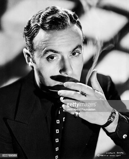 Portrait of actor Charles Boyer wearing a black shirt and tie and smoking a cigarette for Columbia Pictures 1938