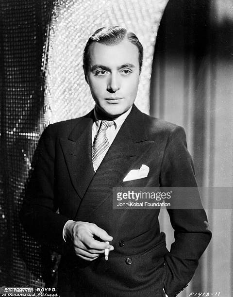 Portrait of actor Charles Boyer wearing a suit and smoking a cigarette for Paramount Pictures 1932