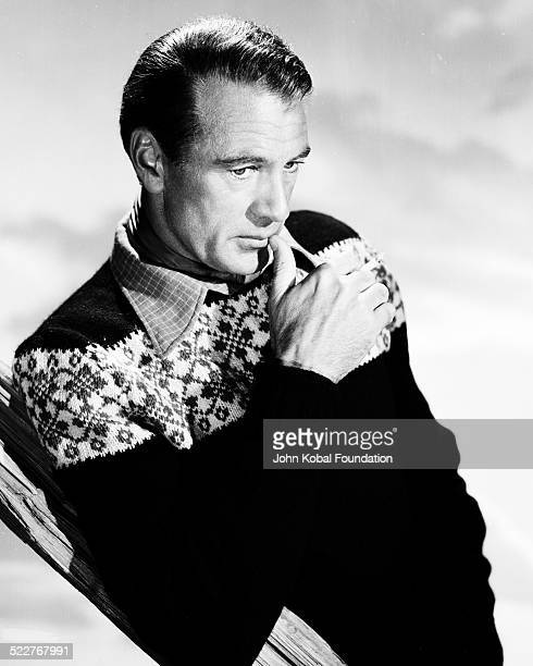 Portrait of actor Gary Cooper wearing a knitted patterned sweater and smoking a cigarette 1955