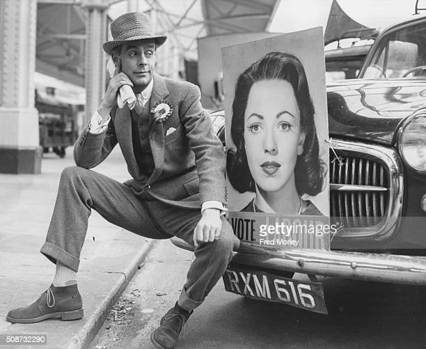 Portrait of actor Ian Carmichael in costume as a Conservative Party candidate sitting on the bumper of a car with a 'Vote Labour' poster bearing the...
