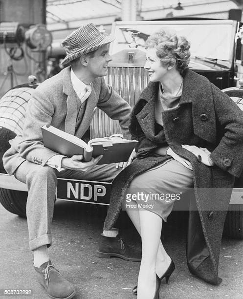 Portrait of actor Ian Carmichael in costume as the Conservative candidate and actress Patricia Bredin as the Labour candidate sitting on a car bumper...