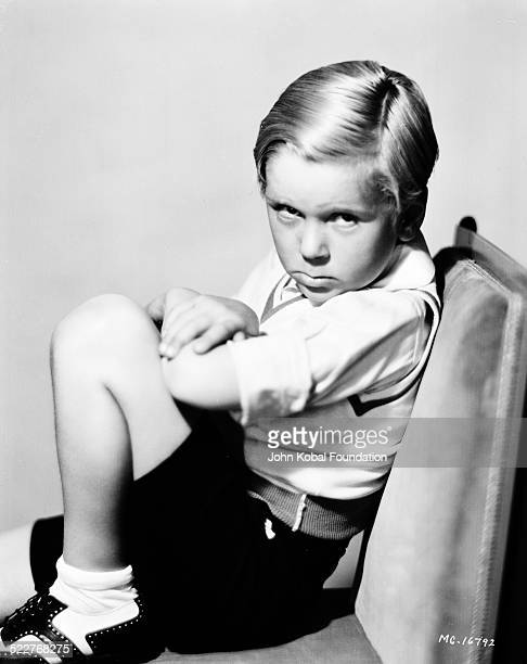 Portrait of actor Jackie Cooper sitting on a chair and frowning to the camera for MGM Studios 1931