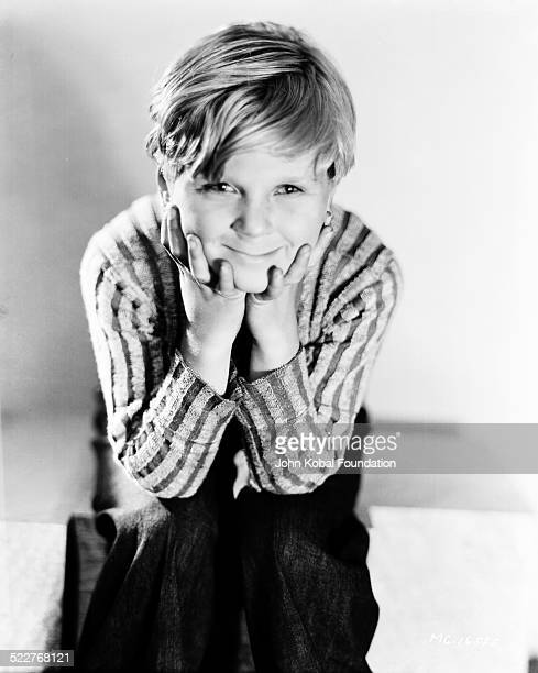 Portrait of actor Jackie Cooper sitting with his chin resting on his hands for MGM Studios 1931