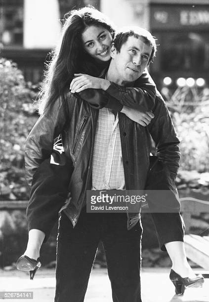 Portrait of actor John Nettles with actress Cecile Paoli on his back both stars of the new television series 'Bergerac' October 7th 1981